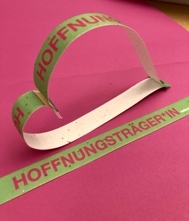 """Papierstreifen mit Samen als Armbänder mit Aufschrift """"Hoffnungsträger*in"""""""